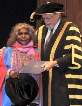 Ms Elizabeth Ellis receiving her award on stage from ANU Vice Chancellor